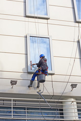 Window washer on a high building. Man washing windows  at height.