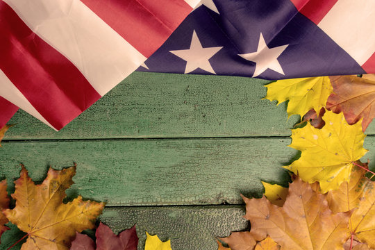 Green vintage wooden background covered with american flag and autumn leaves, copy space