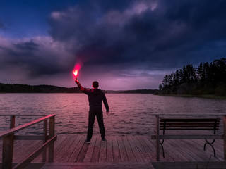 A man at the lake lit the signal bomb. SOS. Help signal. The man at the pier is holding signal block. The man on the quay. Torch with fire. Fototapete