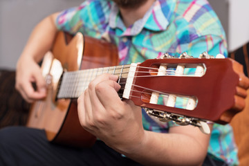 Bearded hipster man hand playing acoustic guitar. Close-up selective focus on hand.