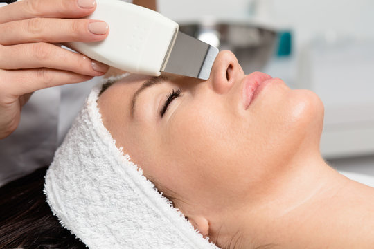 Beautiful woman receiving ultrasound cavitation facial peeling. Skin cleansing procedure at beauty spa salon.