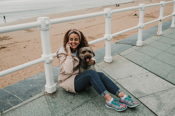 .Young woman wearing a pink coat, playing with her adorable brown spanish water dog while talking on the phone at seafront of Gijon in the north of Spain on a cloudy summer day. Having fun. Lifestyle