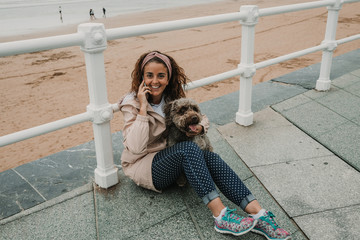.Young woman wearing a pink coat, playing with her adorable brown spanish water dog while talking on the phone at seafront of Gijon in the north of Spain on a cloudy summer day. Lifestyle