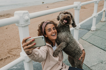 .Young woman wearing a pink coat, playing with her adorable brown spanish water dog and taking selfies on the seafront of Gijon in the north of Spain on a cloudy summer day. Having fun. Lifestyle