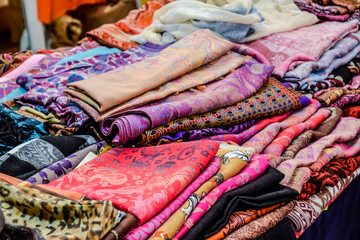 Indian fabrics folded on the counter. Trade in fabrics from india. Fabric with patterns and patterns.