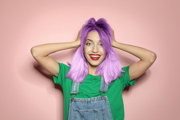Portrait of smiling young woman with dyed straight hair on pink background. Trendy hairstyle design