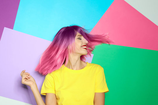 Portrait of smiling young woman with dyed straight hair on colorful background. Trendy hairstyle design