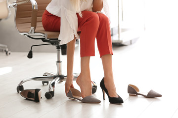 Tired woman taking off shoes at office, closeup view
