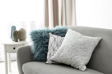Different soft pillows on sofa in room. Interior element