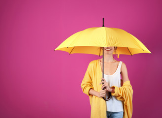 Wall Mural - Woman with yellow umbrella on color background. Space for text
