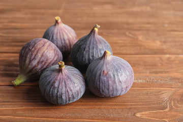 Ripe sweet figs on wooden background. Tropical fruit