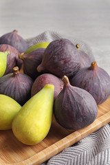 Plate with assorted ripe figs on table. Tropical fruit