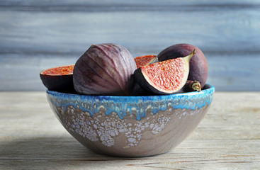 Bowl with fresh ripe figs on wooden background. Tropical fruit
