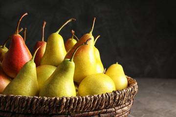 Wicker bowl with ripe pears on table against dark background, closeup