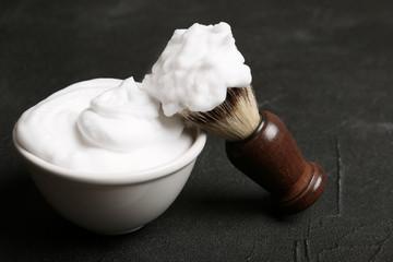 Shaving brush and bowl of foam on dark background