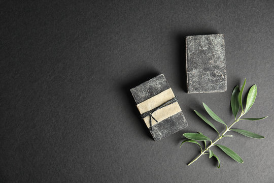 Handmade soap bars with olive twig and space for text on black background, top view