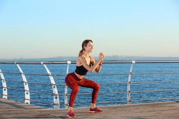 Young woman doing fitness exercises on pier in morning