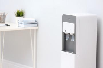 Modern water cooler near light wall in office