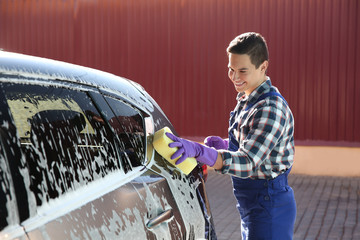 Worker cleaning automobile with sponge at car wash