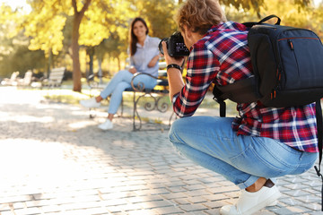 Young male photographer taking photo of model with professional camera in park