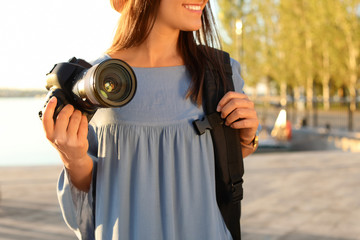 Young female photographer holding professional camera at pier