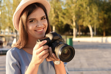 Young female photographer with professional camera on street. Space for text