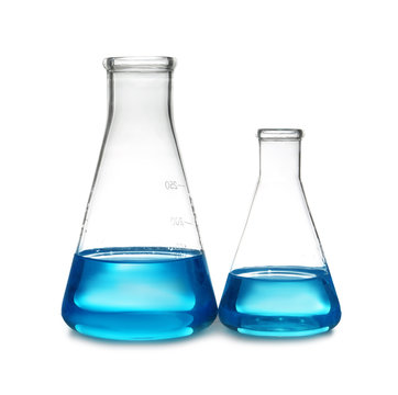 Conical flasks with liquid on table against white background. Laboratory analysis