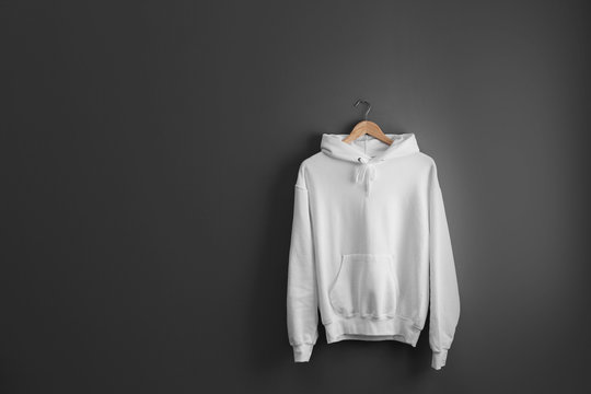 New hoodie sweater with hanger on grey wall. Mockup for design