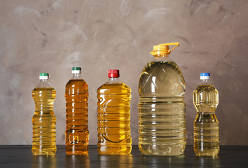 Bottles of oil on table against color background