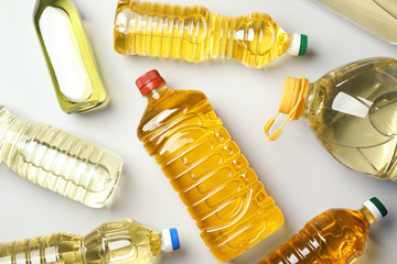 Bottles of oils on light background, top view