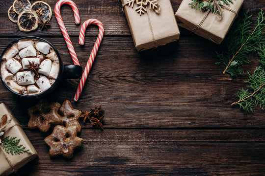 Christmas poster template, composition with gift boxes, mug of hot chocolate, festive candies and gingerbread cookies on wooden background. Creative greeting card. Winter holidays celebration concept