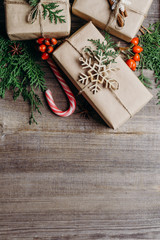 New Year festive background, Christmas composition with decorated gift boxes, evergreen branches and candies, copy space. Creative greeting card. Winter holidays celebration concept