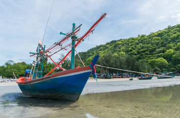 Blue Fishing Boat on Sea Sand with Green Mountain at Khao Kalok Beach Thailand