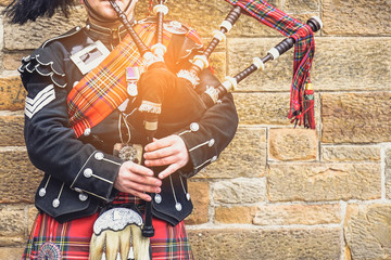 EDINBURGH, SCOTLAND, 24 March 2018 , Scottish bagpiper dressed in traditional red and black tartan dress stand before stone wall. Edinburgh, the most popular tourist city destination in Scotland.. Wall mural