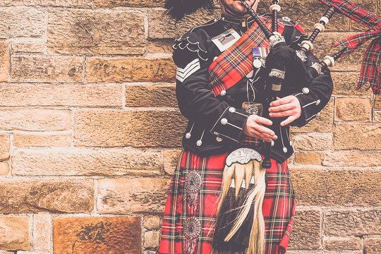 EDINBURGH, SCOTLAND, 24 March 2018 , Scottish bagpiper dressed in traditional red and black tartan dress stand before stone wall. Edinburgh, the most popular tourist city destination in Scotland..