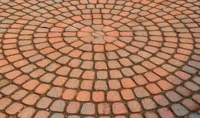 Red circular paved bricks with dirty moss