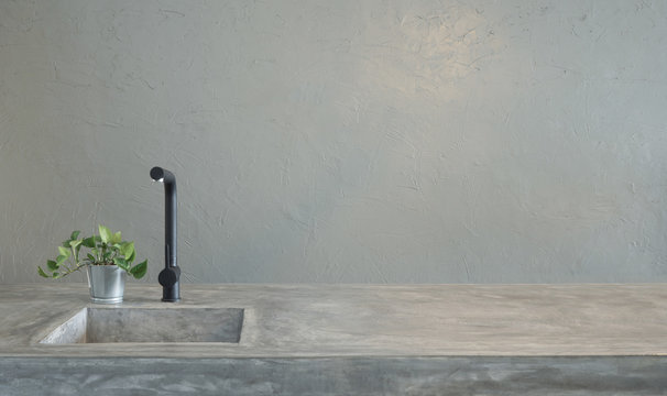 Modern black faucet and kitchen room sink with cement countertops and green grass .