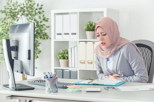 muslim businesswoman having stomachache at work