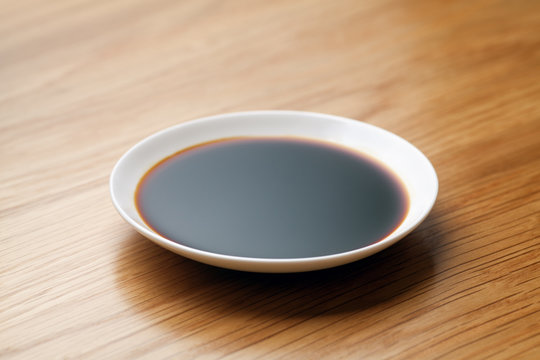 Dish of soy sauce on the wooden table