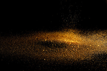 Sprinkle glitter gold dust sand in the dark textured abstract background elegant for Merry...