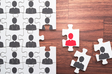 Human resource management. Selecting right people for organization's success. Personnel, employment and recruitment concept. Assembling jigsaw puzzle on wood desk.