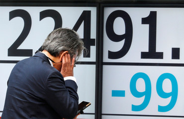 A man uses a mobile phone in front of an electronic board showing Japan's Nikkei average outside a brokerage in Tokyo