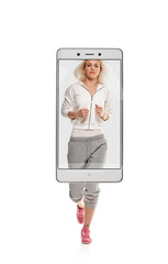 Young attractive healthy woman doing workout and running, concept virtual reality of the smartphone. going out of the device