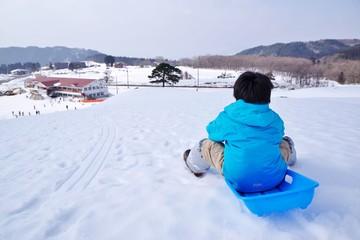 スキー場でそり遊びをする子供
