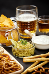 beer and a bowl of guacamole with nachos and salty snacks on an old black wooden table in a pub