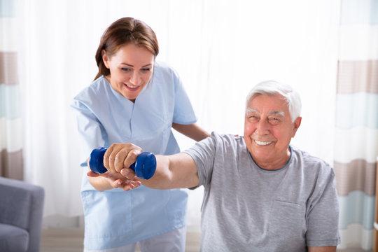 Nurse Helping Senior Man With Dumbbell Exercise