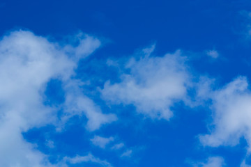 Blue sky background with tiny clouds. White fluffy clouds in the blue sky.