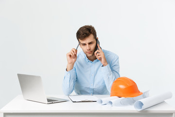 Confident architect. Handsome young man with hardhat and blueprint and talking on the mobile phone while sitting in his office.