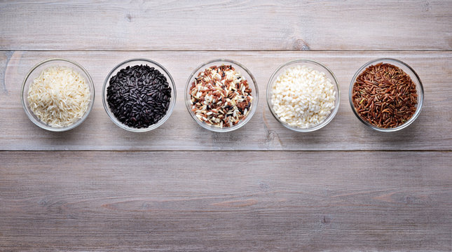 Five types of rice: basmati, black rice, mix long grain, arborio and red rice. Space for text, top view