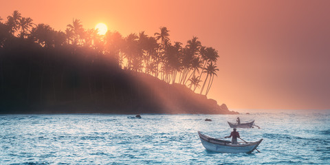 Tropical beach on sunset with fishermen and sea